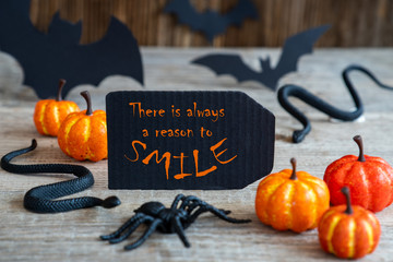 Black Label With English Quote There Is Always A Reason To Smile. Scary Halloween Decoration Like Bat, Snake And Spider