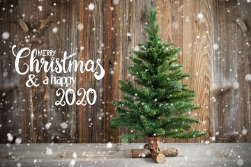 English Calligraphy Merry Christmas And Happy New Year 2020. Christmas Tree Infront Of Brown Wooden Background And Snow
