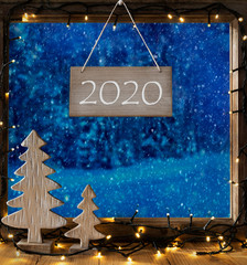 Sign With Text 2020. Window Frame With Winter Landscape With Snow. View To Snowy Trees Outside With Snowflakes. Christmas Tree And Fairy Lights.