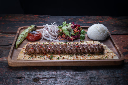 Turkish lula lamb or beef kebab with rice and vegetables isolated on rustic wooden table