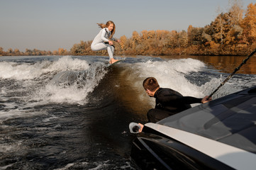 Photographer taking pictures from the motorboat of the girl riding on the wake surf