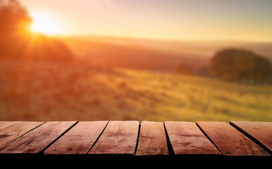 A wooden table top planks product display with a blurred background scene of farmland at sunset.