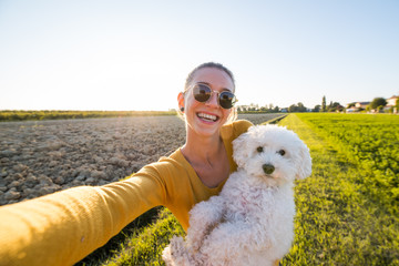 Young and beautiful woman taking a selfie with her dog at the park