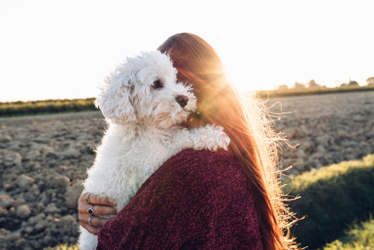 Woman hugging her dog at the field at sunset