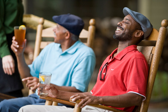 Laughing mid-adult man sitting in a wooden chair next to his father.