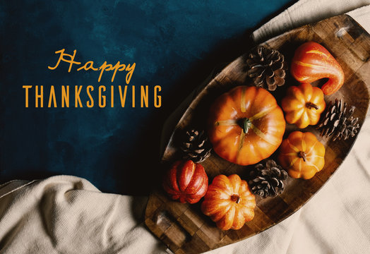 Happy Thanksgiving text on autumn pumpkin flat lay background.