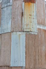 Gebogene Fassade aus verrostetem Wellblech an einem alten Getreidespeicher