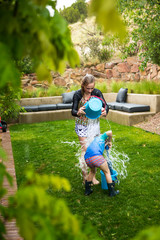 A teenage girl and her brother having a water fight in the garden, emptying buckets of water over each other.