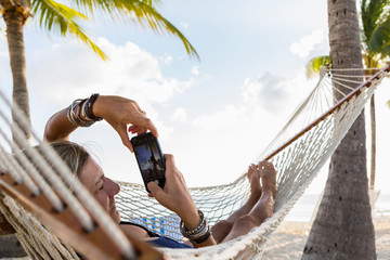Woman taking picture with smartphone while lying on hammock