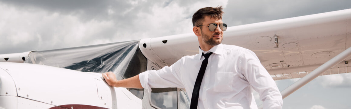 panoramic shot of confident pilot in sunglasses standing near plane