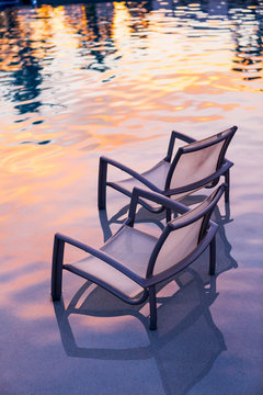 Deck chairs in pool during sunset