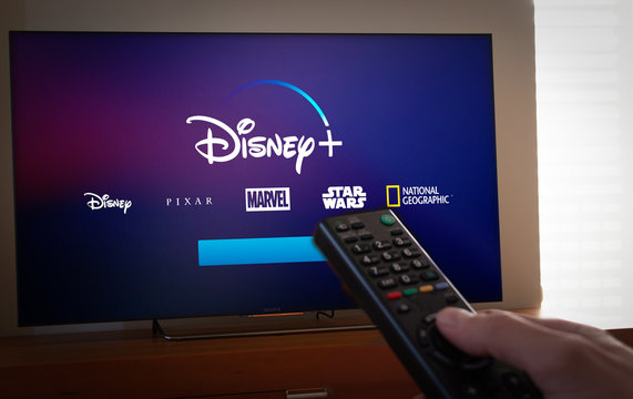 Barcelona, Spain. January 2019: Man holds a remote control With the new Disney + screen on TV