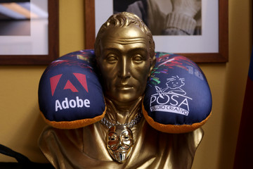 The corporate logos of software company Adobe and Posa Studio school are seen in a travel pillow around a Simon Bolivar statue in Caracas