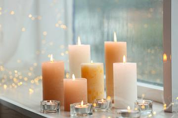 Fototapeta Beautiful burning candles and fairy lights at windowsill on rainy day obraz