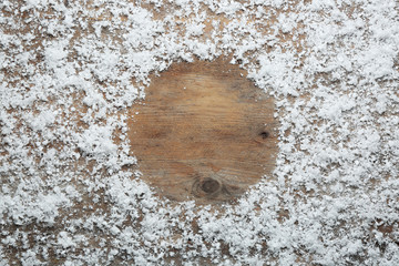 Frame made of snow on wooden background, top view with space for text. Winter season