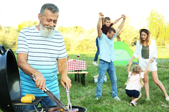 Happy senior man cooking food on barbecue grill and his family in park