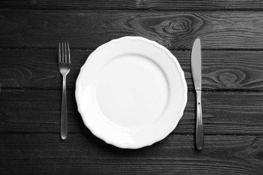 Elegant table setting on black wooden background, flat lay