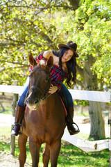 Young pretty girl riding a horse , lens flare