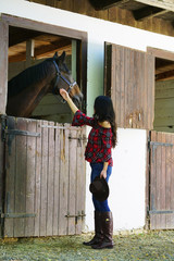 Cowgirl looking at her horse in a barn