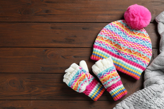 Warm knitted clothes on wooden background, flat lay. Space for text