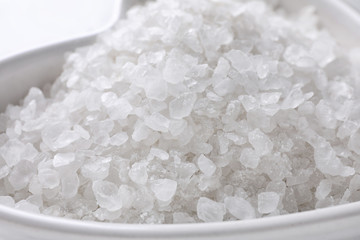 Natural white sea salt in bowl, closeup view. Spa treatment