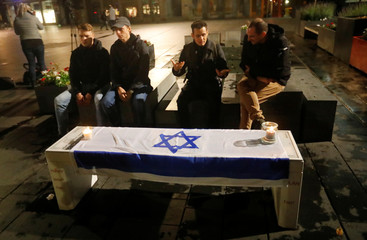 People sit near an Israeli flag with lit candles on it at central market square in Halle