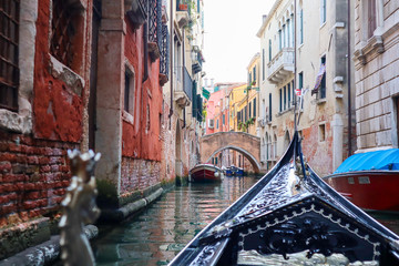 A gondola sails through a small canal in Venice, Italy