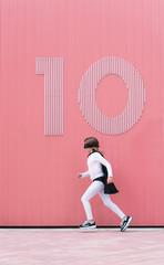 Girl in superhero costume running along a wall