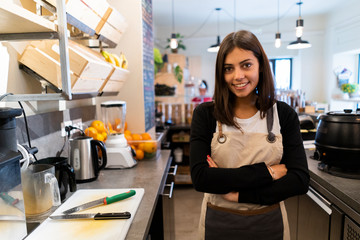 Portrait of confident young woman behind the counter in a cafe