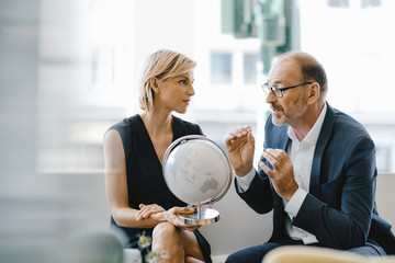 Businessman and woman sitting in coffee shop, looking at globe, discussing business