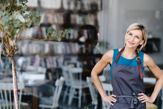 Portrait of blond woman, standing in front of her own coffee shop