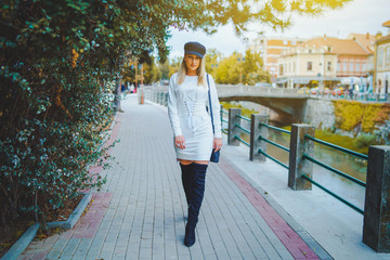 Young confident blonde beautiful woman wearing white dress and black boots and hat walking on the sidewalk pavement by the river in a autumn day in the town or city