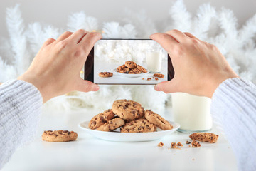 An anonymous blogger holds a smartphone to take a picture of some delicious handmade chocolate chip cookies and a glass of fresh milk at Christmas. Lifestyle concept, social networks and cooking blogs