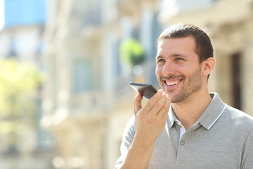 Happy man using voice recognition on phone to send a message