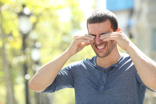Adult man scratching itchy eyes in the street