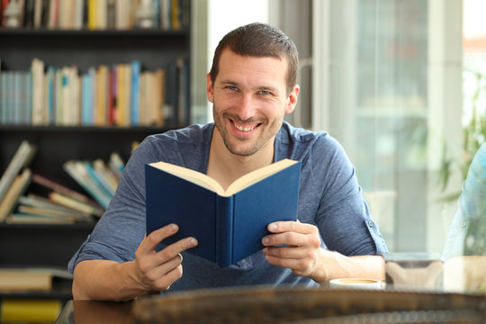 Happy man holding a paper book posing looking at camera