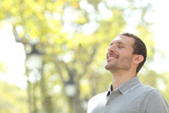 Happy casual man breathing fresh air in a park