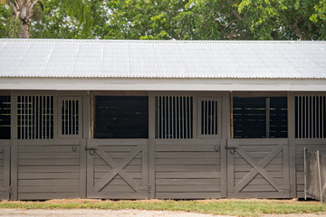 Horse stable on a farm made of wood with trees in background