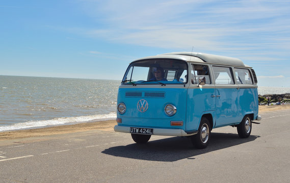 Classic Blue and white VW camper van being driven along Felixstowe seafront promenade.