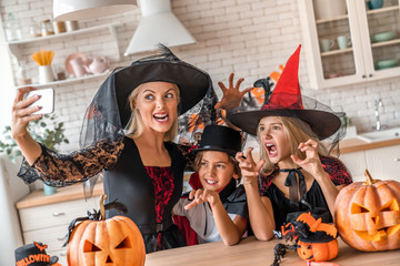 Smiling young woman taking selfie and having fun with her kids in Halloween decorated kitchen