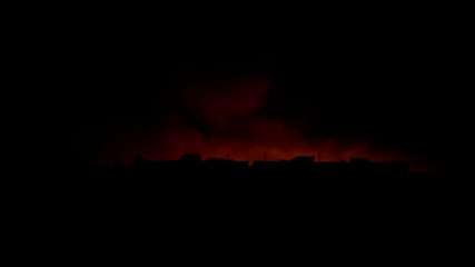 Light from fires and smoke are seen billowing out behind buildings in Tel Abyad