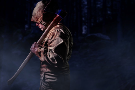 Murderer with an axe in dark woods.