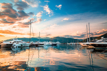 Luxury yachts and motor boats docked in marina Porto Montenegro in Mediterranean sea at sunset.