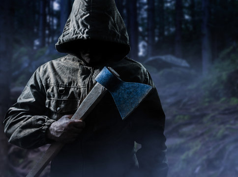 Scary killer with an axe in woods.