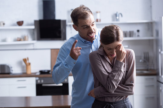 aggressive man in shirt screaming at crying wife during quarrel
