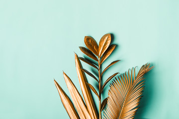 Tropical palm leaves painted with gold paint on delicate pastel mint background