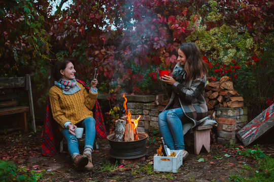 three friends relax comfortably and drink wine on an autumn evening in the open air by the fire in the backyard.