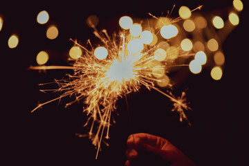Hand holding sparkler and light bokeh background.Abstract and brightly colorful firework in the celebration and anniversary festival.Merry Christmas and New year party light over night sky.
