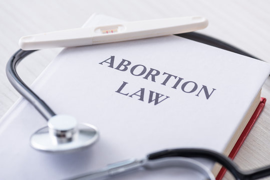 selective focus of pregnancy test on book with abortion law lettering near stethoscope