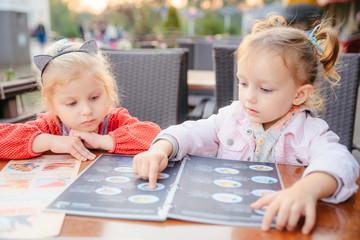little girl sitting in cafe choosing food from menu